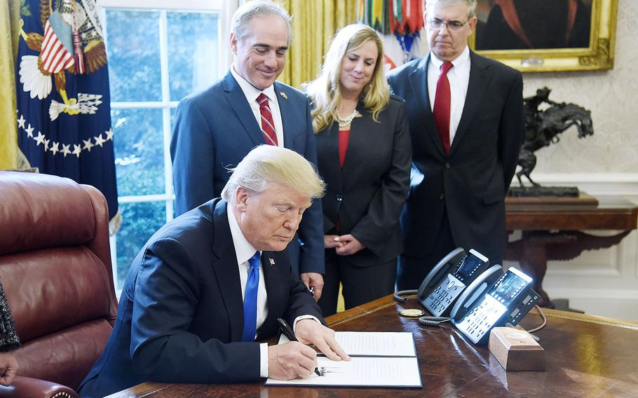 """President Donald Trump signs an Executive Order on """"Supporting our Veterans during their Transition from Uniformed Service to Civilian Life"""" on Tuesday, January 9, 2018 in the Oval Office of the White House in Washington, D.C."""