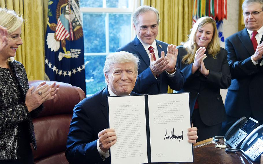 """President Donald Trump holds a signed Executive Order on """"Supporting our Veterans during their Transition from Uniformed Service to Civilian Life"""" on Tuesday, January 9, 2018 in the Oval Office of the White House in Washington, D.C."""