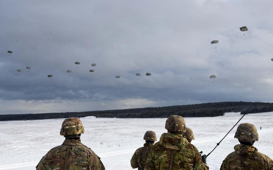 Soldiers with the 173rd Brigade Combat Team (Airborne) watch as fellow soldiers parachute to the ground during an exercise at Grafenwoehr, Germany, on Wednesday, Jan. 17, 2018.