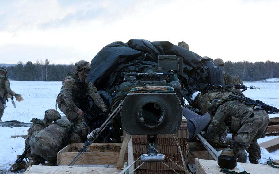 Soldiers with the 173rd Brigade Combat Team (Airborne) assemble an M777 155mm Howitzer that parachuted to the ground during an exercise at Grafenwoehr, Germany, on Wednesday, Jan. 17, 2018.