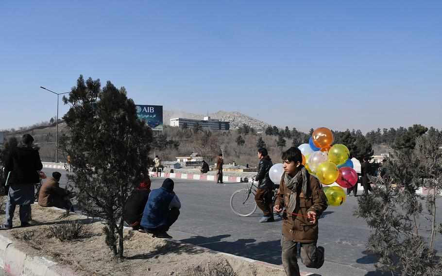 A boy carried balloons across a road in front of the Intercontinental Hotel in Kabul, Afghanistan, on Sunday, Jan. 21, 2018, as security forces worked to clear the building of Taliban attackers. Blasts and gunfire could be heard Sunday morning, more than 15 hours into the attack.