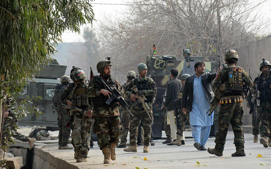 Uniformed and plainclothed Afghan security forces patrol the site of a deadly suicide attack in Jalalabad, east of Kabul, Afghanistan, Wednesday, Jan. 24, 2018.