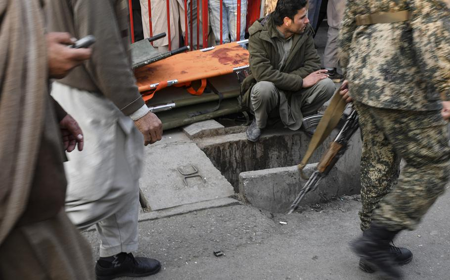 An Afghan man waits, smoking, beside a pile of stretchers outside Emergency hospital in Kabul, Afghanistan, on Saturday, Jan. 27, 2018, following a ambulance-borne bomb blast earlier in the day in a busy part of town. The attack left dozens dead and more than 150 wounded.