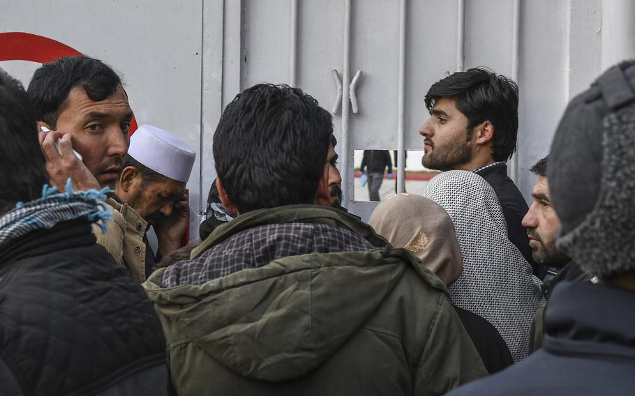Men and women crowd the gates of Emergency hospital in Kabul, Afghanistan, on Saturday, Jan. 27, 2018, seeking news of loved ones after a deadly ambulance-borne bomb blast earlier in the day. Casualties from the blast strained the hospital's capacity as they arrived in piles in the back of ambulances.