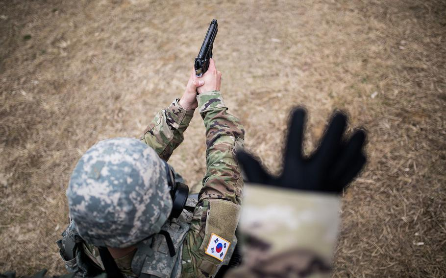 A 19th Expeditionary Sustainment Command best warrior competitor fires a pistol during a stress shoot at Masan, South Korea on Wednesday, March 7, 2018.