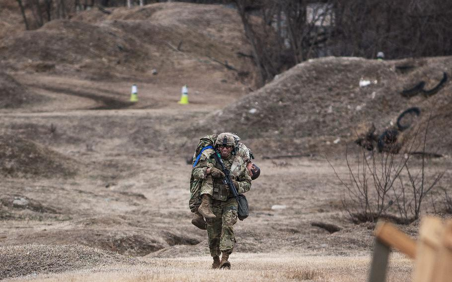Sgt. Gerardo Saavedra, 94th Military Police Battalion, 19th Expeditionary Sustainment Command best warrior competitor carries a training dummy during a stress shoot at Masan, South Korea on Wednesday, March 7, 2018.