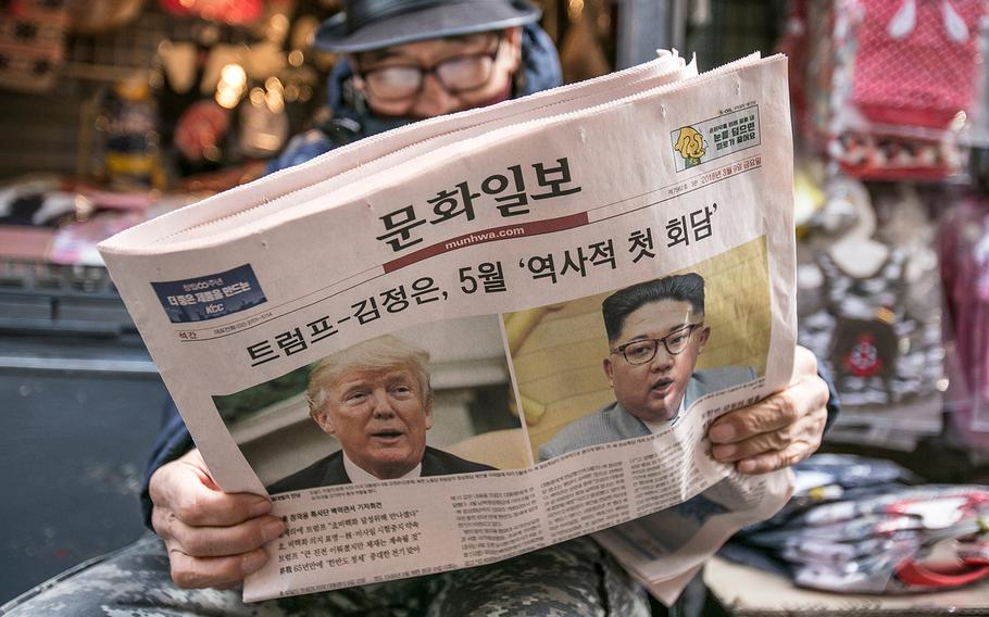A man reads a copy of the Munhwa Ilbo newspaper featuring President Trump and North Korean leader Kim Jong Un on the front page in Seoul on March 9, 2018.