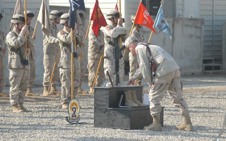 A solider lays a device on a battlefield cross erected for Spc. Dwayne McFarlane, who was killed in Iraq on Jan. 9, 2005. The nonprofit behind the effort to establish a national memorial dedicated to the Global War on Terror got a new director Monday, April 9, 2018.