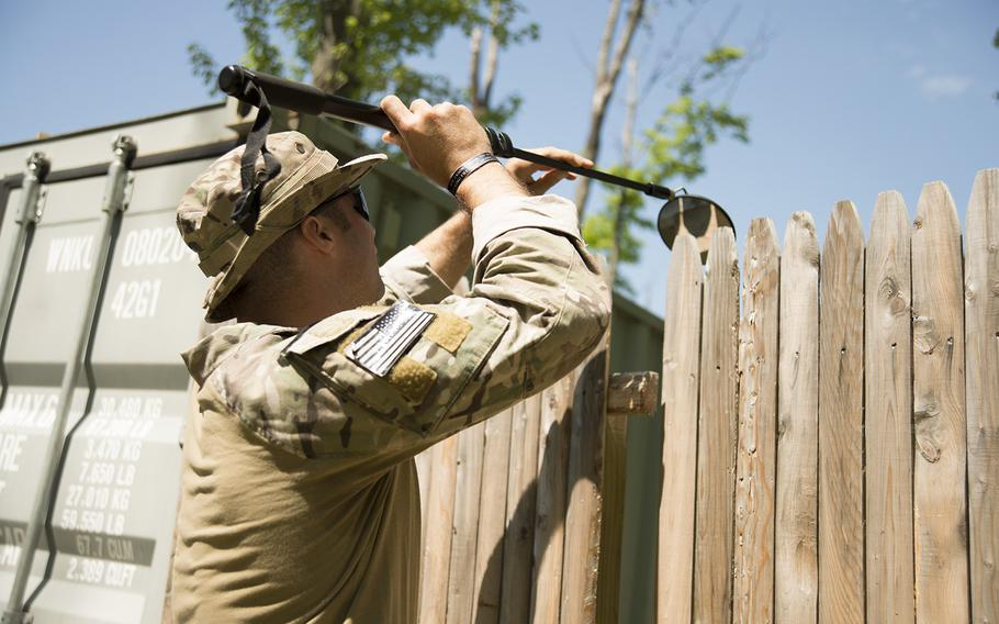 Maj. Daniel O'Neil, from 158th Fighter Wing Explosive Ordnance Disposal, sweeps a fence with a mirror to see what is behind it during a training scenario at the Ethan Allen Firing Range, Jericho, Vt., May 27, 2015.