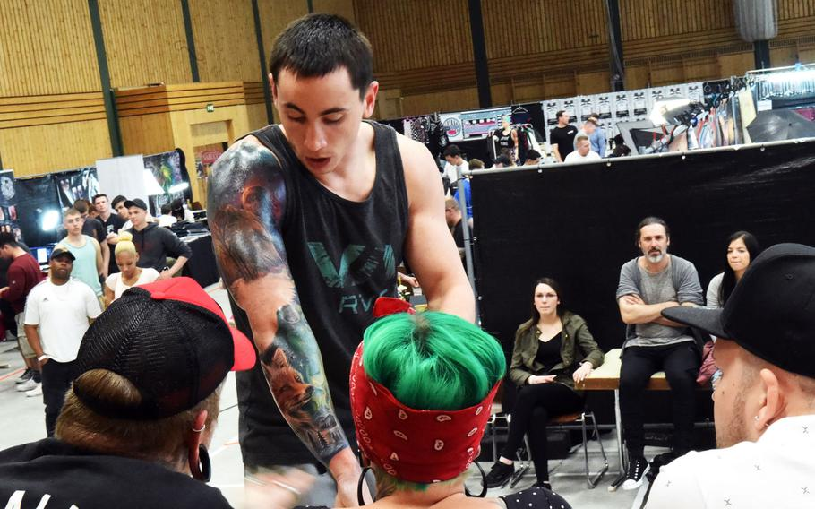 Sgt. Jared Taylor, a scout with the 2nd Cavalry Regiment, shows his new fox tattoo to the judges at the Tattoo Expo Grafenwoehr, in Grafenwoehr, Germany on Sunday, April 15, 2018. Taylor ended up winning best color tattoo.