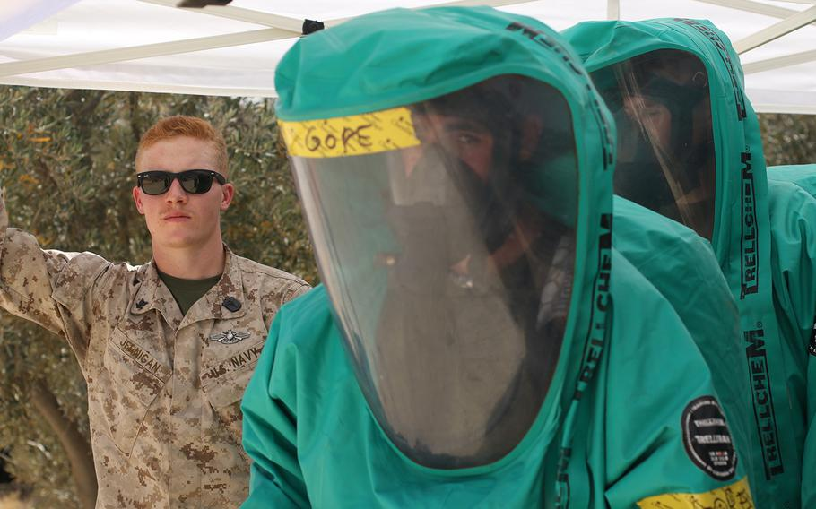 Petty Officer 3rd Class Corey Jernigan, a U.S. Navy hospital corpsman, looks on as U.S. Marines prepare take samples during a chemical, biological, radiological, nuclear training exercise, May 10, 2017, during Exercise Eager Lion at the Joint Training Center in Jordan.