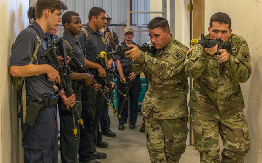 Instructors with the 14th Military Police Brigade demonstrate proper room clearing techniques to explorers during the Bi-Annual National Law Enforcement Explorers Academy. A member of the brigade at Fort Leonard Wood, Mo. has been granted religious accommodation to have a beard because of his of the Norse Pagan faith.
