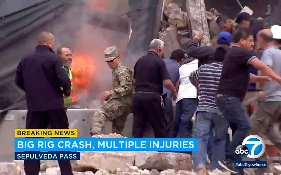 Bystanders rush to rescue people trapped in wreckage as flames break out after a big rig gravel hauler and cars collided on southbound Interstate 405 near the Mulholland Bridge on the west side of Los Angeles, Monday, April 30, 2018.