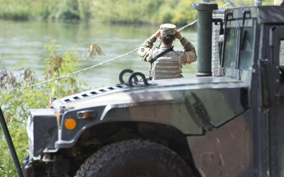 A soldier from the Texas National Guard scans the shores of the Rio Grande River in Starr County, Texas, April 10, 2018 as part of the federal call-up to the Texas-Mexico border.