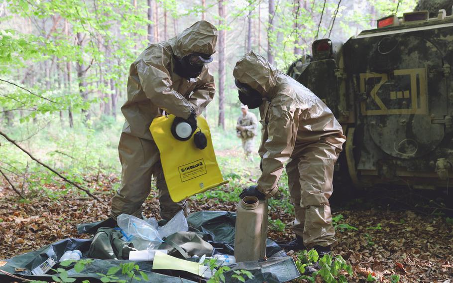 U.S. Army Master Sgt. Timothy Brogan, background, watches as Pfc. Alec Ervin and Pfc. Alex Rojas of Company C, 1st Battalion, 63rd Armor Regiment, prepare to test a tactical decontamination concept at Joint Warfighting Assessment 18, Hohenfels, Germany, Thursday, May 3, 2018.