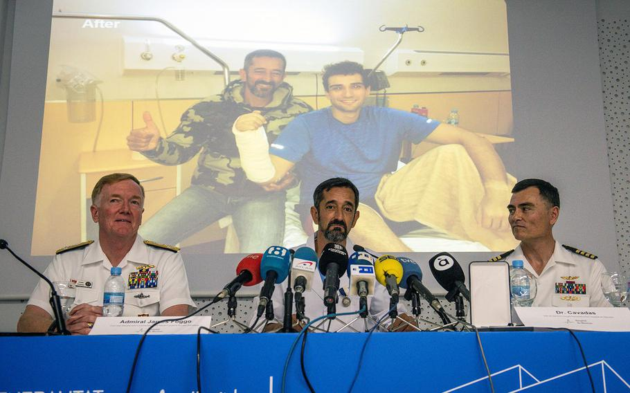 A photo of Dr. Pedro Cavadas posing with a sailor whose hand was amputated is projected on a screen. In hte foreground, Adm. James G. Foggo III, commander of U.S. Naval Forces Europe-Africa and commander of Allied Joint Force Command Naples, Italy, left; Cavadas, a neurosurgeon at Hospital de Manises in Valencia, Spain, center; and Capt. Michael McGinnis, U.S. Naval Forces Europe-Africa Force Surgeon, answer questions at the hospital May 4, 2018.