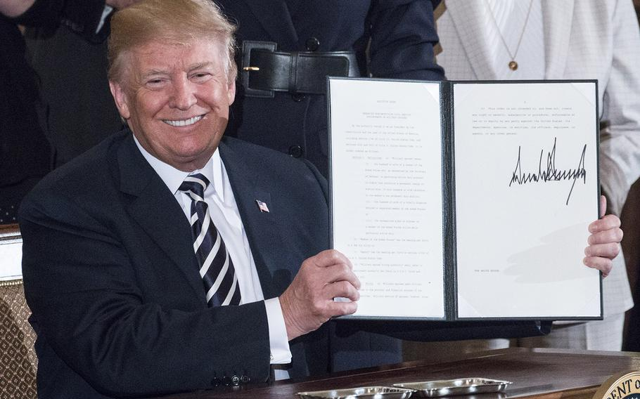 President Donald Trump holds up an executive order he's just signed encouraging federal agencies to hire more military spouses during a ceremony at the White House, May 9, 2018.