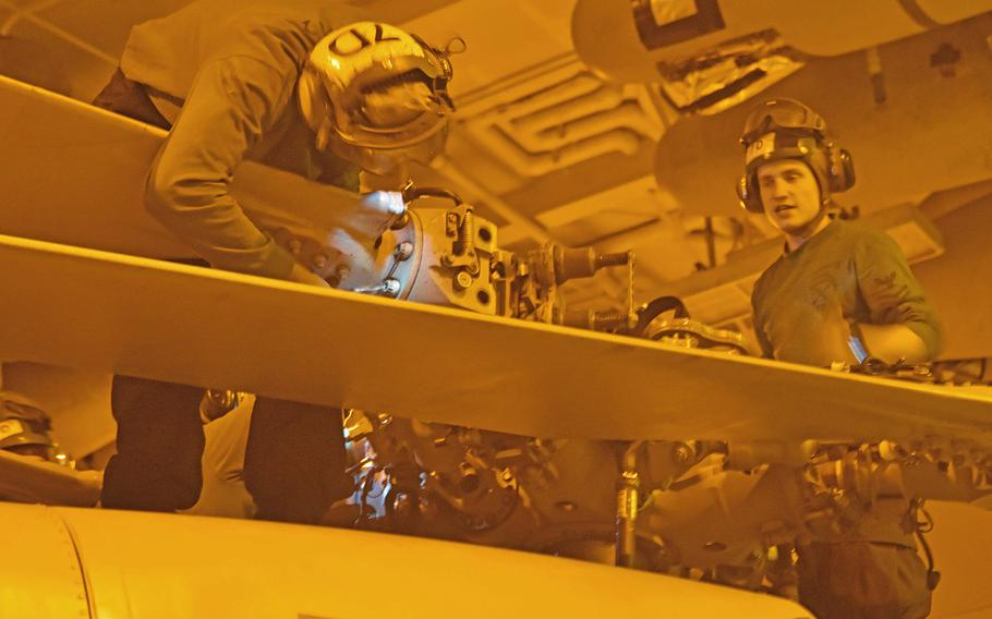 A night crew works on a helicopter rotor in the USS Harry S. Truman's hangar bay on May 7, 2018. The Truman is deployed in the eastern Mediterranean to fight the Islamic State for Inherent Resolve.