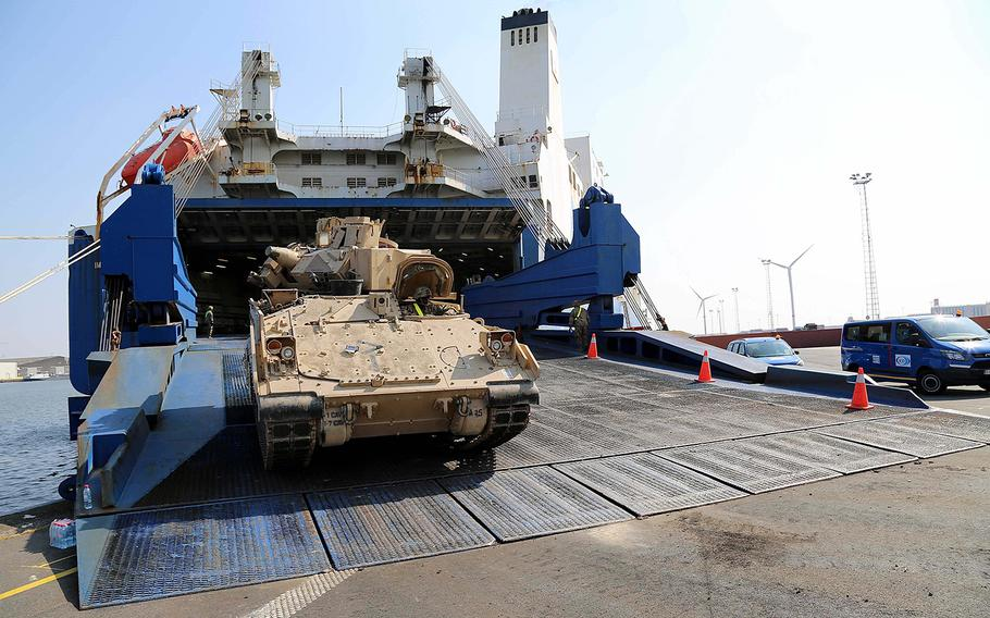 A soldier drives an M2 Bradley Fighting Vehicle from the 1st Armored Brigade Combat Team, 1st Cavalry Division, down the ramp of a cargo vessel in Antwerp, Belgium, Sunday, May 20, 2018.