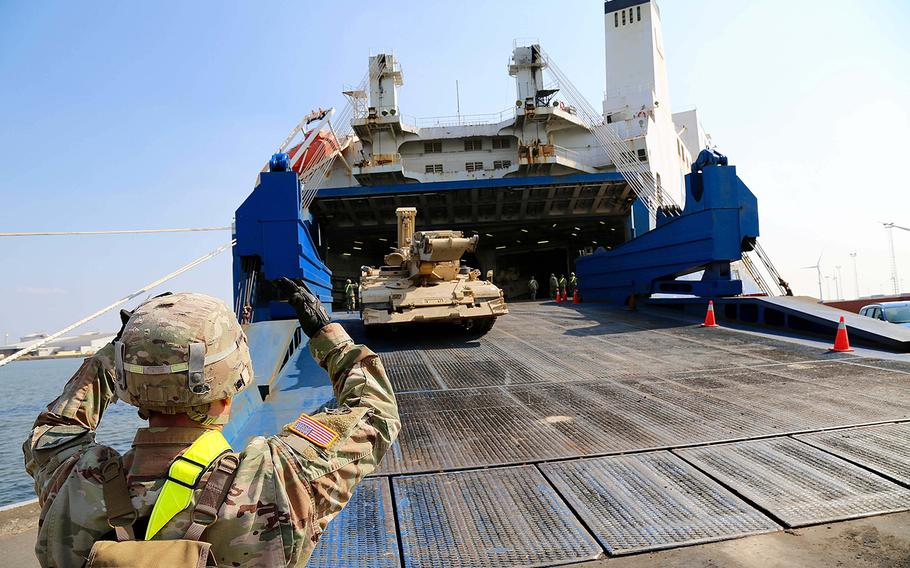 A soldier directs a tracked vehicle off the cargo vessel Endurance in Antwerp, Belgium, on Sunday, May 20, 2018. The vehicle was one of some 395 tracked vehicles that are being offloaded in Antwerp's port in support of Atlantic Resolve an ongoing NATO deterrence operation.