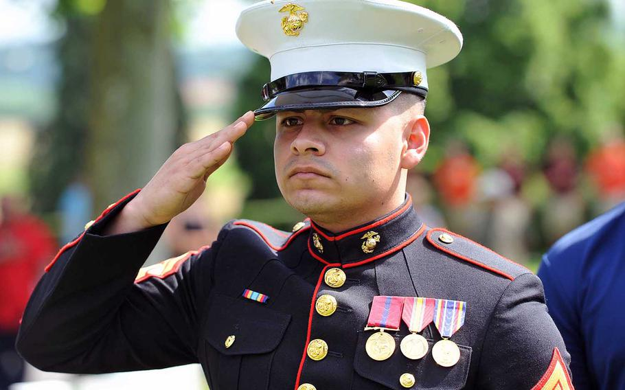 Marine Sgt. Kimsaim Garcia salutes during the playing of the national anthems during the Memorial Day ceremony at Aisne-Marne American Cemetery in Belleau, France, Sunday, May 27, 2018.. Garcia is attached to the U.S. embassy in Brussels, Belgium.