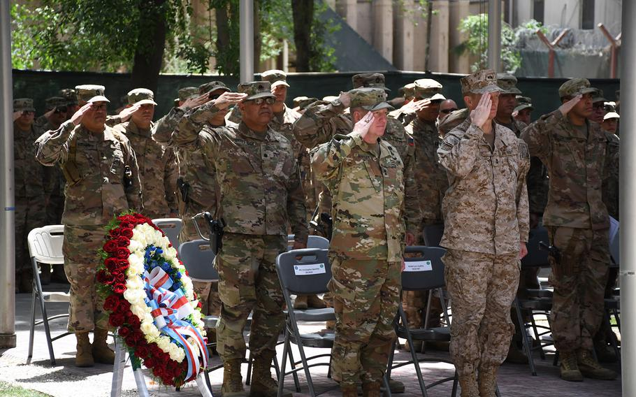 Troops salute during a Memorial Day ceremony at Resolute Support headquarters in Kabul, Afghanistan, on Monday, May 28, 2018.