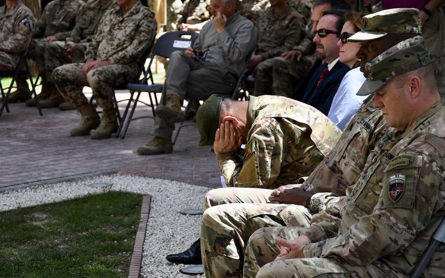 Afghanistan's National Security Council Sgt. Major Roshan Safi holds his head in his hands during an emotional Memorial Day event at NATO's Resolute Support mission headquarters in Kabul, Afghanistan, on Monday, May 28, 2018.
