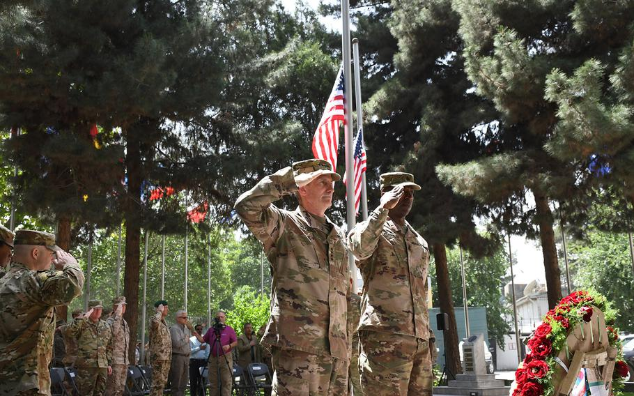Gen. John Nicholson, commander of the U.S.-led NATO mission in Afghanistan, and Command Sgt. Major David Clark, his senior enlisted advisor, salute during the playing of taps after placing a Memorial Day wreath in front of a monument at NATO's Resolute Support mission headquarters in Kabul, Afghanistan, on Monday, May 28, 2018.