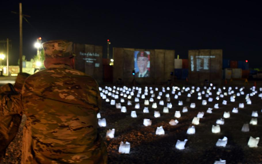 """A soldier views a Memorial Day display called """"Faces of the Fallen,"""" which featured hundreds of luminaries and a slideshow of images, videos and names of U.S. servicemembers who have died in America's wars since 2001. The temporary monument was near the Bagram Air Field PX and the site of a November 2016 attack that killed five Americans and wounded 15 others the day after Veterans Day. Photographed on Monday, May 28, 2018."""