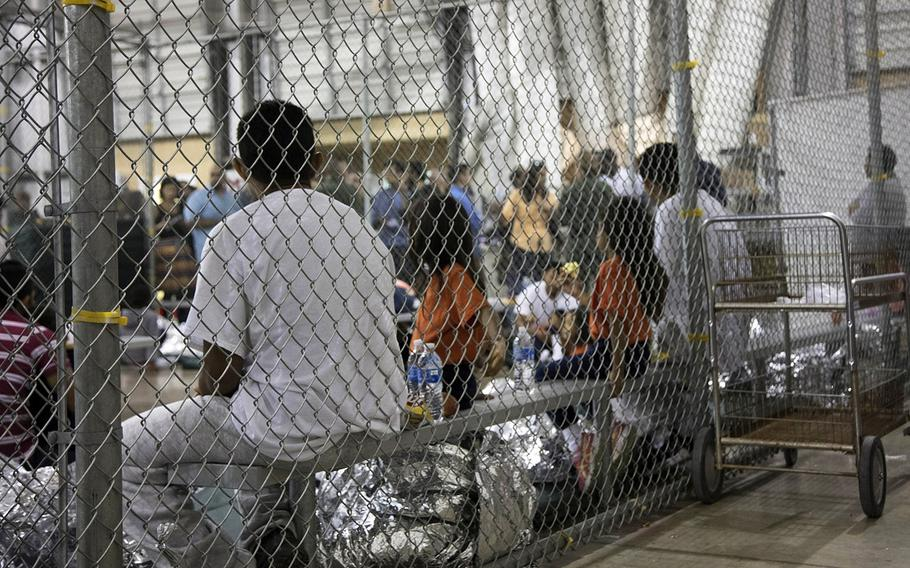 In this June 17, 2018 photo provided by U.S. Customs and Border Protection, people who have been taken into custody related to cases of illegal entry into the United States are shown at a facility in McAllen, Texas.