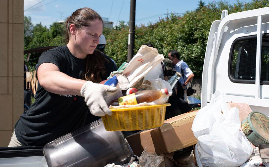 Cpl. Carlye Rehmann, an accident investigator with the provost marshal at Marine Corps Air Station Iwakuni, loads water-logged items into the back of a truck for disposal in the Shuto area of Iwakuni, Japan, on July 12, 2018.