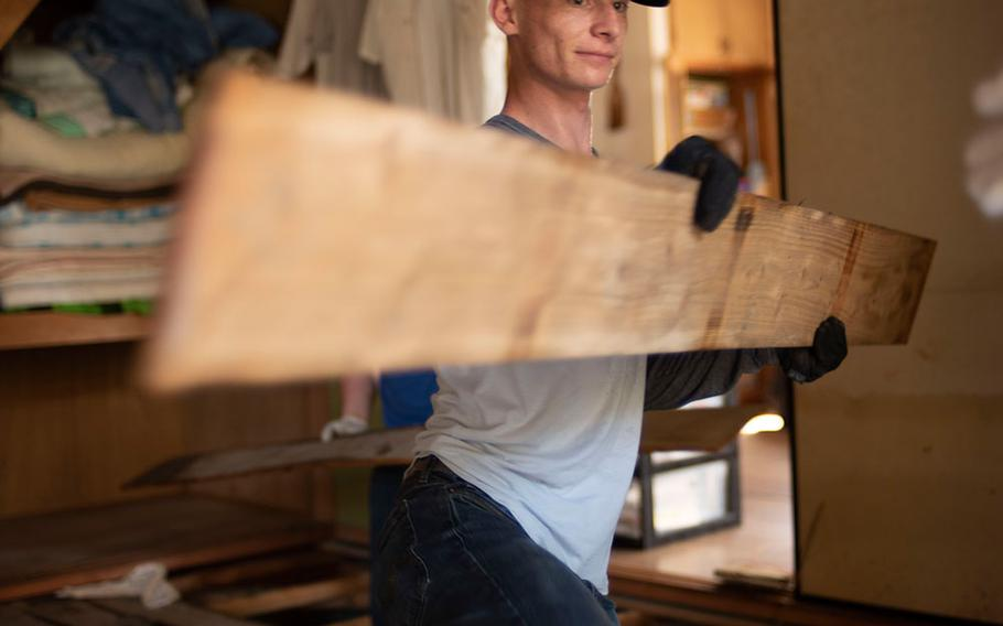 Lance Cpl. Gavin Pitzer, a Marine police officer at Marine Corps Air Station Iwakuni, hands saturated floorboards to fellow Marines during clean-up and relief operations in the Shuto area of Iwakuni, Japan, on July 12, 2018.