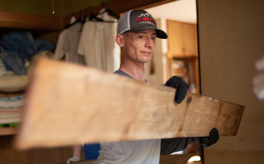 Lance Cpl. Gavin Pitzer, a Marine police officer at Marine Corps Air Station Iwakuni, hands saturated floor boards to fellow Marines during clean-up and relief operations in the Shuto area of  Iwakuni, Japan, on July 7, 2018.