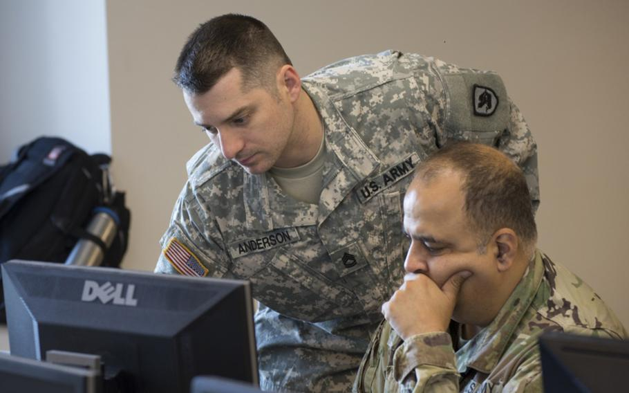 Sgt. 1st Class Samuel Anderson, with the Washington National Guard, advises Cpt. Sameer Puri, 56th Theater Information Operations Group, at Highline Community College in Des Moines, Wash., on July 6. 2018.
