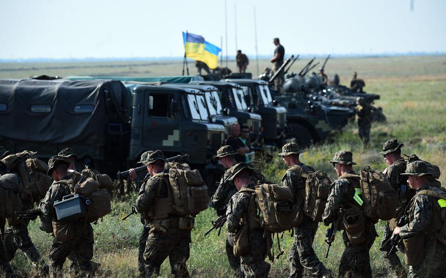 U.S. Marines walk past a row of Ukrainian vehicles during exercise Sea Breeze, Thursday, July 12, 2018.