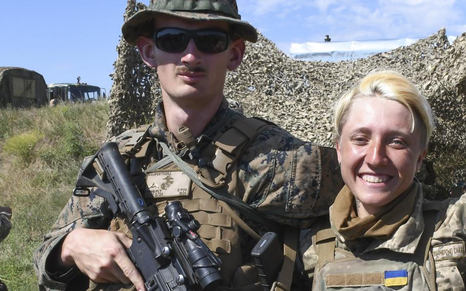 Pictured here while preparing for a company attack as part of Exercise Sea Breeze on Saturday, July 14, 2018, from left to right are Lance Cpl. Robert Haupertkeill and Pvt. Kristina Nikkolaeva. Nikolaeva and Hapuertkeill had exchanged some gear earlier in the week in a sign of friendship and Nikolaeva had promised to present her U.S. counterpart with an aquamarine beret when the exercise ended.
