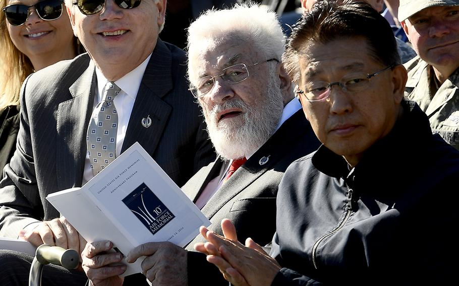 Adrian Cronauer, center, references the event program during the Air Force Memorial's 10th anniversary ceremony in Arlington, Va., Oct. 14, 2016.