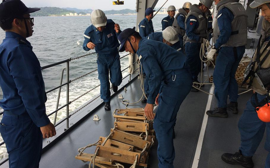 Members of the Japan Self-Defense Force prepare a ladder used to help a team lower in the water to investigate a nearby ship during Pacific Shield 2018 on July 25, 2018.