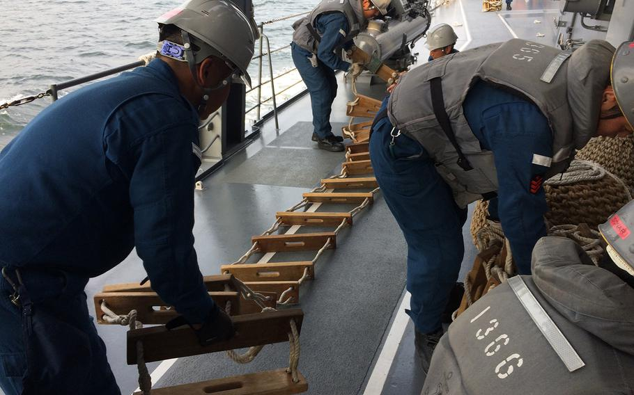 Members of the Japan Self-Defense Force prepare a ladder used to help an investigative team board a nearby ship during Pacific Shield 2018 on July 25, 2018.