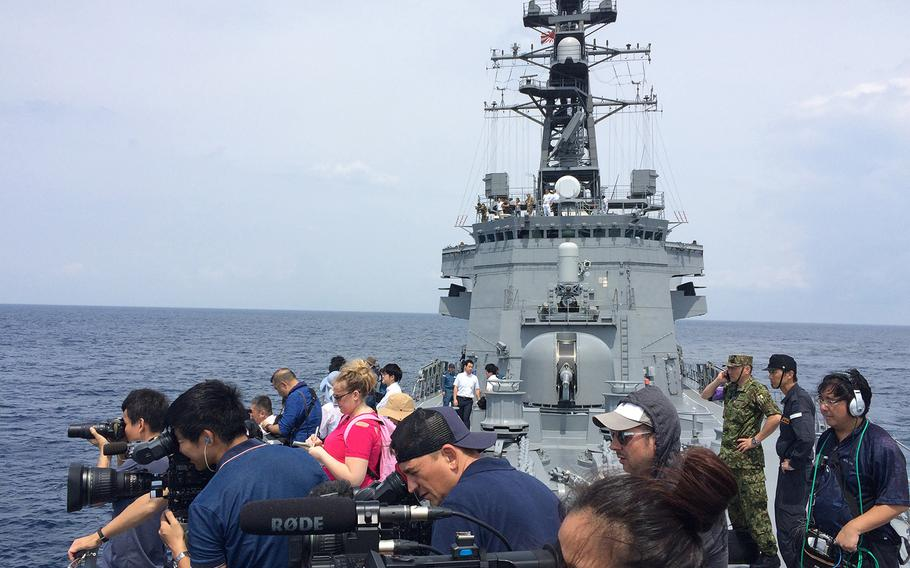 Reporters embedded with the Japan Self-Defense Force take photographs during Pacific Shield 2018 on July 25, 2018.