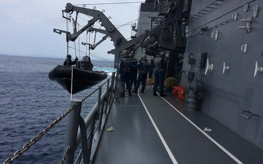 Members of the Japan Self-Defense Force prepare to lower into the water to investigate a nearby ship during Pacific Shield 2018 on July 25, 2018.