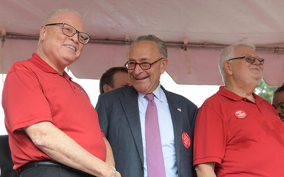 Sen. Chuck Schumer, D-N.Y., (center) on stage during a rally for the American Federation of Government Employees on July 25, 2018 in Washington, D.C.