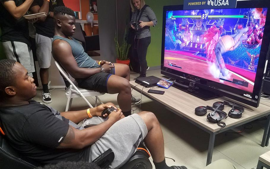 Sgt. Kalyntae Williams, top, and Sgt. Deveon Landfair, soldiers with the Army's Second Cavalry Regiment, play the final round of Street Fighter V, at the E-game tournament at Grafenwoehr, Germany, Saturday, July 28, 2018. Williams beat Landfair, and will now be traveling to Seattle to compete in the PAX West Gaming Convention.