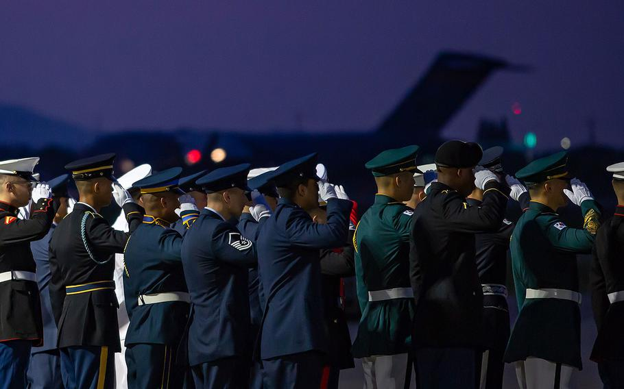 A multinational honor guard salutes an Air Force transport plane as it attempts to take off from Osan Air Base, South Korea to Hawaii, Wednesday, Aug. 1, 2018.