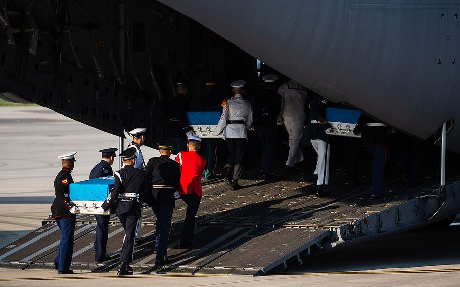 A multinational honor guard loads three caskets onto an Air Force transport plane at Osan Air Base, South Korea for their trip to Hawaii on Wednesday, Aug. 1, 2018.