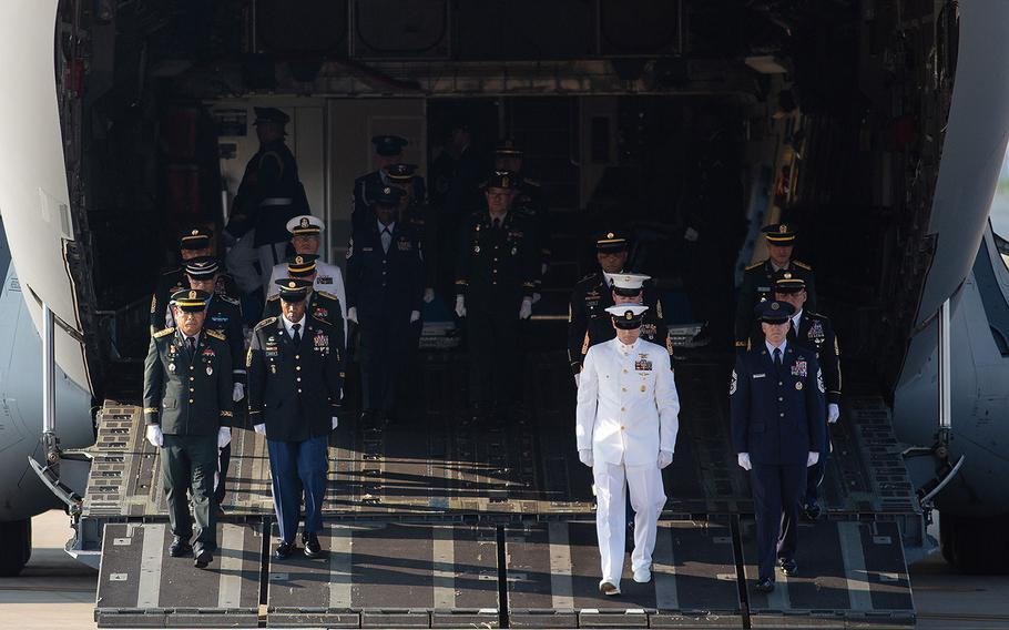 A multinational honor guard walks off an Air Force transport plane at Osan Air Base, South Korea on Wednesday, Aug. 1, 2018. Fifty-five cases presumed to be holding the remains of U.S. troops killed in the Korean War began their journey home Wednesday after a formal send-off on base.