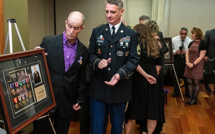 Retired Army Staff Sgt. Michael Thomas Jeffrey, left, reacts with surprise after seeing a glass-encased framed board with his military service medals presented to him as a gift after he received a Purple Heart during a ceremony in Washington D.C. on Purple Heart Day on Tuesday, Aug. 7, 2018. Applauding is Jeffrey's brother, Army Sgt. 1st Class Joe Jeffrey.