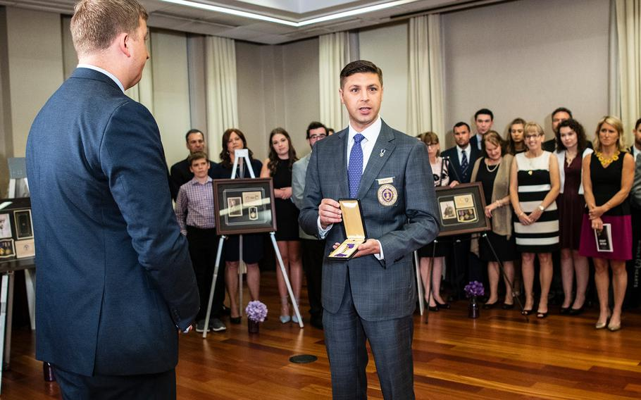 Aleks Morosky, the National Legislative Director of the Military Order of the Purple Heart, presents a recently discovered medal to Purple Hearts Reunited founder Army National Guard Maj. Zacharia Fike during a ceremony in Washington D.C. on Purple Heart Day on Tuesday, Aug. 7, 2018.