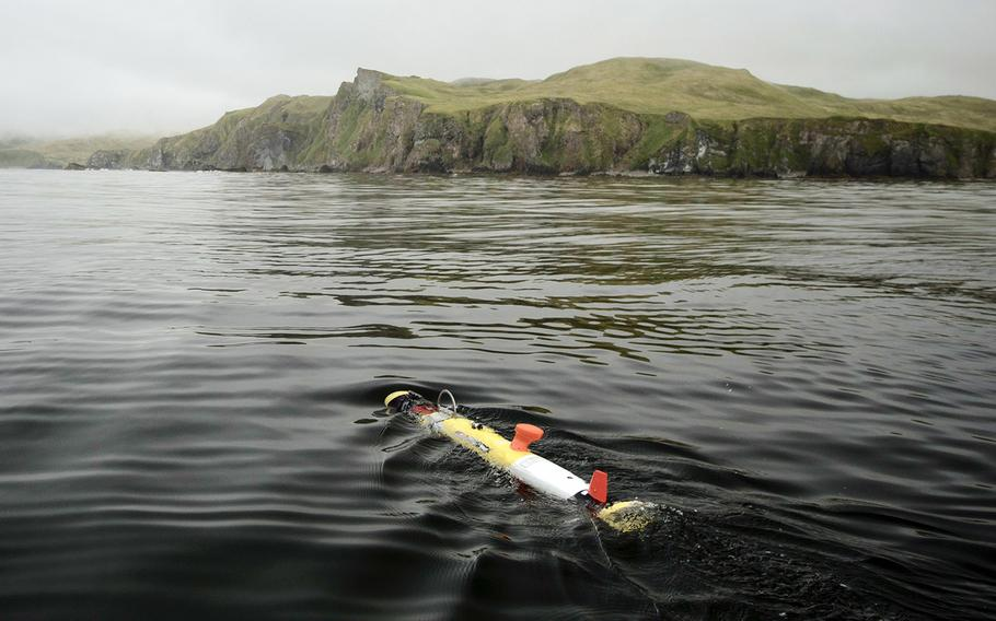 An underwater vehicle glides away from a research boat before diving beneaththe surface, where it spent the next six hours systematically scanning the seafloor near Kiska, an island in Alaska. Underwater vehicles were used to help locate the missing stern of the USS Abner Read on July 17.