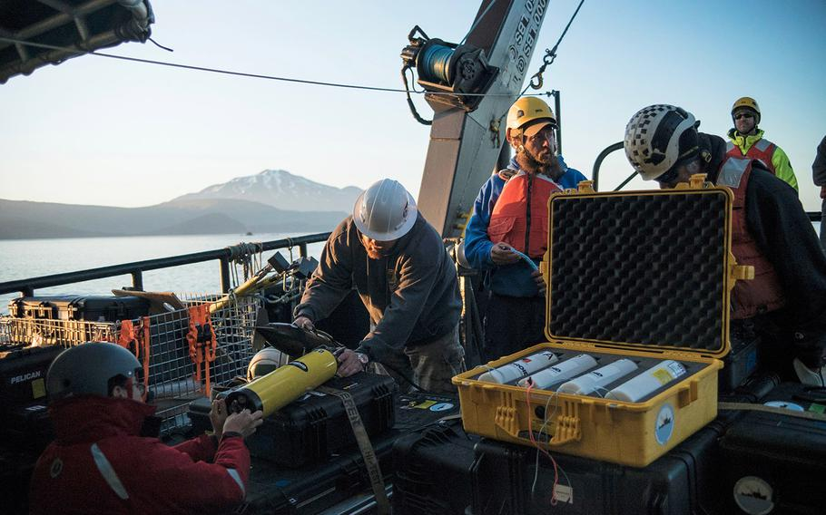 Project Recover members Bob Hess, Brian Kim, and Matt Breece test an acoustic transponder, which was used during aseafloor searchto findWorld War II wreckage in the Aleutian Islands.